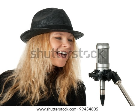 Female singer in black hat singing with studio microphone. Isolated on white background. - stock photo
