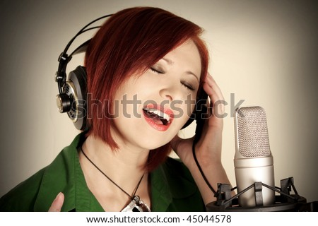 Female singer with headphones recording in studio - stock photo