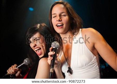 Female singers performing, soft and hard duet - stock photo