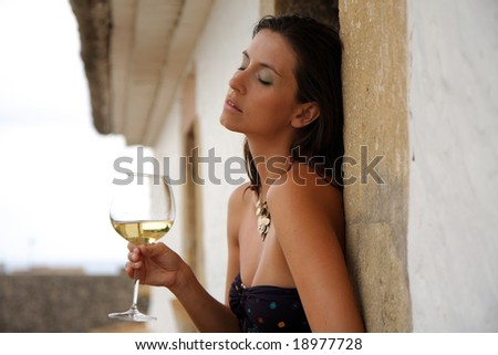 Female sitting on the roof of antic building with wine - stock photo