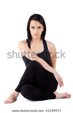female sitting with legs crossed doing exercise, looking at camera