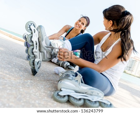 Female skaters putting on their skates outdoors - stock photo