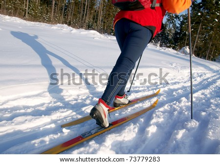 Female skier casts a long shadow on snow on a sunny day - stock photo