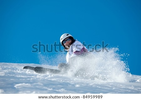 Female skier coming down the slope - stock photo