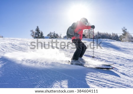 Female skier dressed in red jacket enjoys slopes in Italy with sun behind her. - stock photo