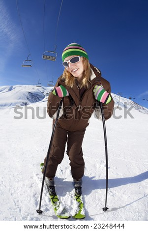female skier leaning on sticks and smiling - stock photo