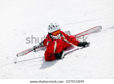 Female skier looking at the camera after falling down on mountain slope - stock photo