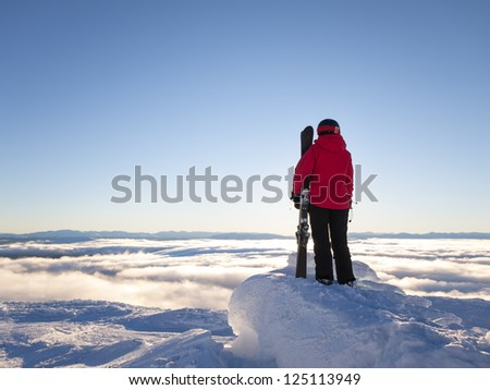 Female skier looking out over cloud covered valley.