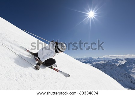Female skier on a steep slope with mountainraing and sun in the background