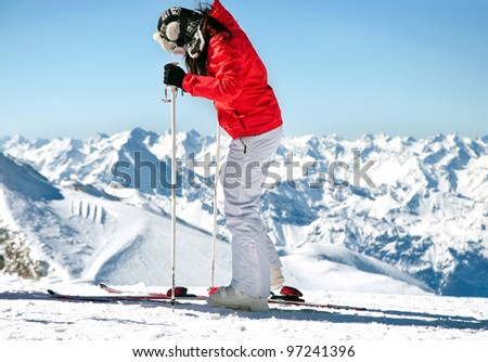 Female skier on ski slope in european alps with mountain background - stock photo