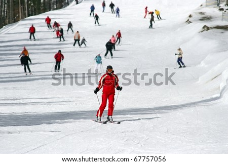 Female skier skiing down a wide track for beginners - stock photo