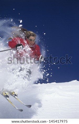 Female skier skiing through powdery snow on ski slope against clear blue sky - stock photo