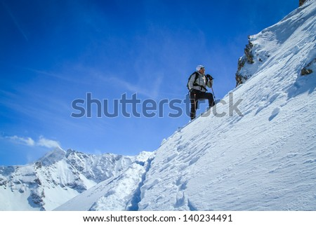 Female skier standing on steep slope with mountains in background.