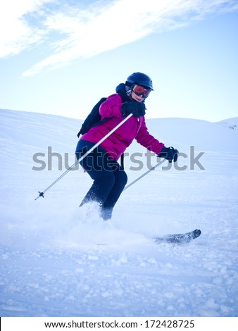Female skier with helmet in the Austrian Alps - stock photo