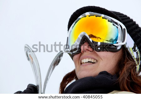 female skier with skis smiling and wearing ski glasses - stock photo