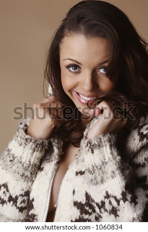 Female smiling and holding sides of winter coat