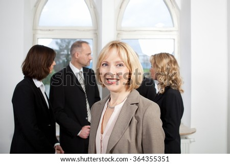 Female smiling businesswoman in front of her colleagues