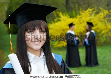 female smiling graduate student in the spring park after finishing education with diploma