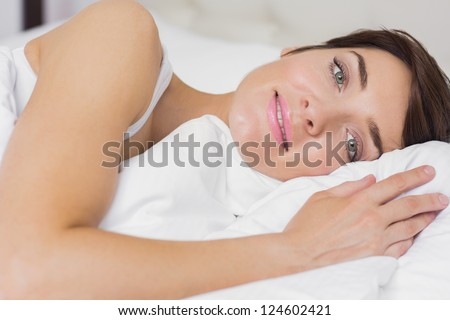 Female smiling in bed in hotel room