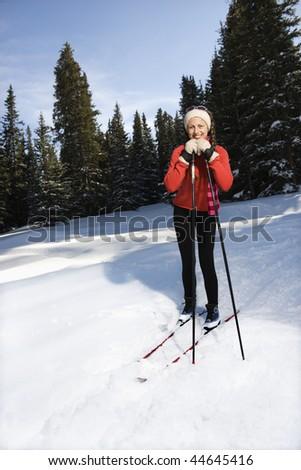 Female snow skiier smiling, standing in the snow leaning on ski poles.  Vertically framed shot. - stock photo