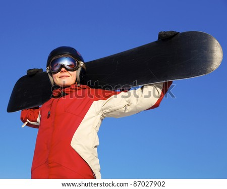 Female snowboarder against bright blue sky