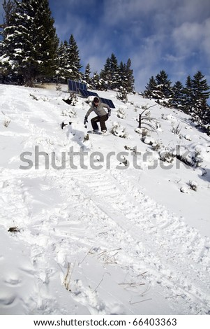 Female Snowboarder Catching Some Air - stock photo