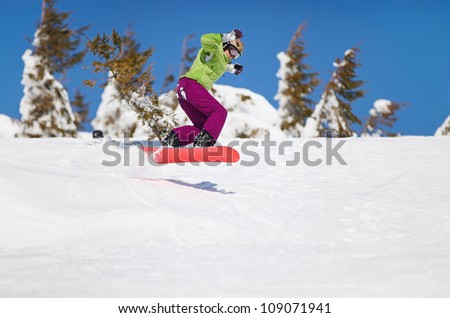 Female snowboarder jumping on mountain slope - stock photo