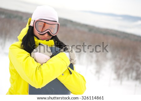 Female snowboarder on the top of the hill