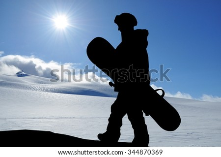 Female snowboarder silhouette high in mountains. Young woman carrying her snowboard to the hill, snowy hills and sun behind her. - stock photo
