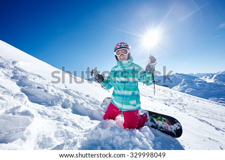 Female snowboarder wearing colorful helmet, blue jacket, gloves and pants sitting on snowy slope and showing thumb up hand gesture with both hands against alpine landscape - winter sports concept - stock photo