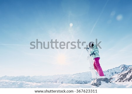 Female snowboarder wearing colorful helmet, blue jacket, grey gloves and pink pants standing with snowboard in her hands and preparing for ride - snowboarding concept - stock photo