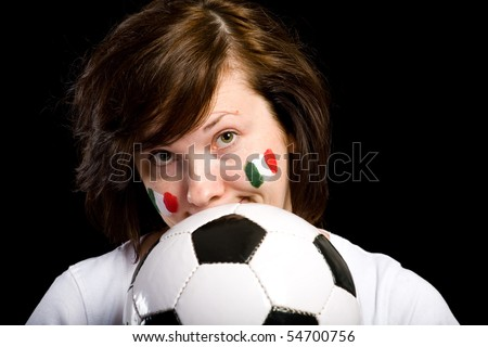 female soccer fan holds soccer ball in front of her, italian flags on her cheeks, studio shoot isolated on black background