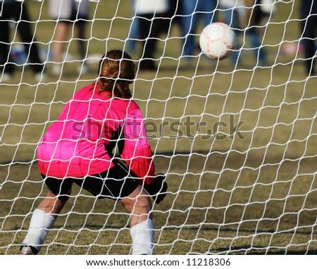 Female Soccer Goalie prepares to stop a goal - stock photo