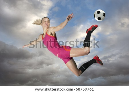 Female soccer player kicking a ball in midair. - stock photo