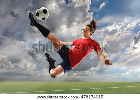Female soccer player kicking ball outdoors