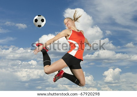 Female soccer player kicks a ball in mid air. - stock photo