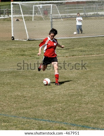 Female Soccer player takes a direct kick - stock photo