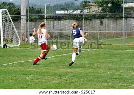 Female soccer player takes a shot past a defender - stock photo