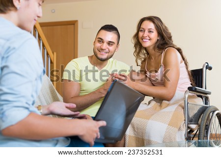 Female social worker consulting smiling young woman in invalid chair and husband. Focus on man - stock photo