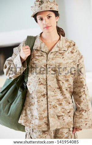 Female Soldier With Kit Bag Home For Leave - stock photo