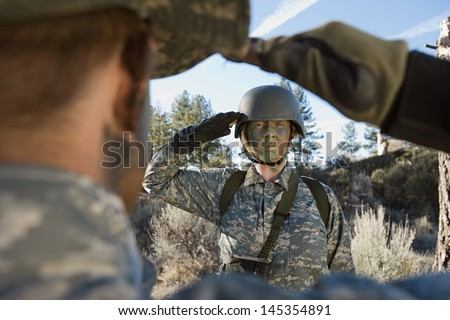 Female solider saluting troop during training session - stock photo