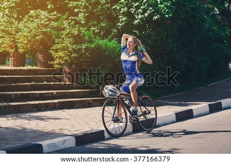 Female sportsman cyclist making stretching at bicycle. Woman cycling on countryside summer sunny road or highway. Training for triathlon or cycling competition. - stock photo