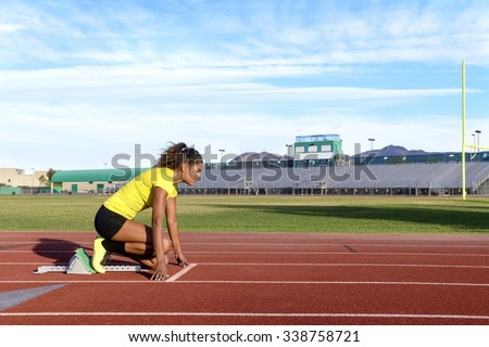 Female Sprinter Getting Ready to Start The Race - stock photo