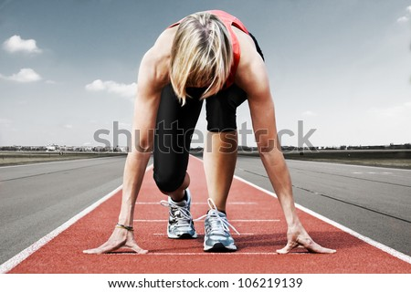 Female sprinter waiting for the start on an airport runway - stock photo
