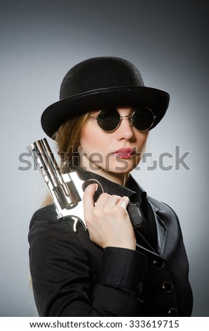 Female spy with weapon against gray - stock photo