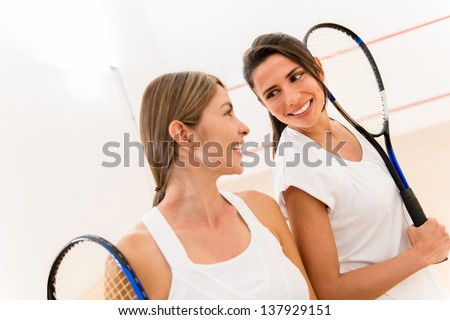 Female squash players at the court holding rackets