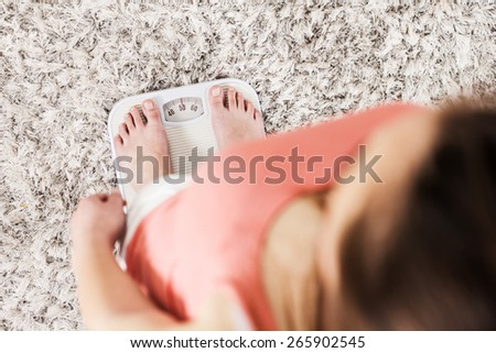 Female standing on scale for measuring. Unrecognizable person. Weight loss concept at home. View from above.                                 - stock photo