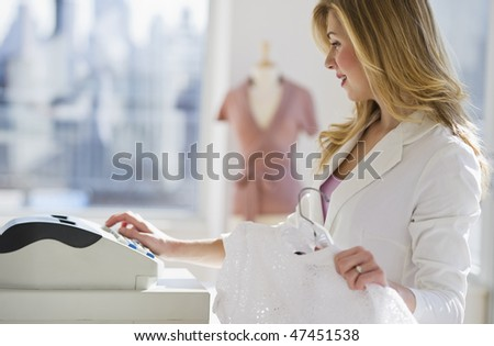 female store employee selling clothing at register