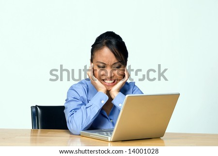 Female student appears mad and frustrated as she frowns at her laptop. Horizontally framed photograph. - stock photo