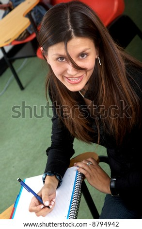 female student at university making notes on a notebook